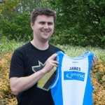 James S holding the team running vest